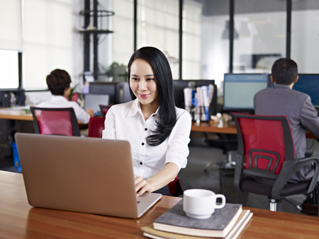 asian office lady: young asian businesswoman working in office using laptop computer with colleagues in background.