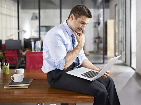 using computer: caucasian business executive sitting on desk using laptop computer in office, side view.