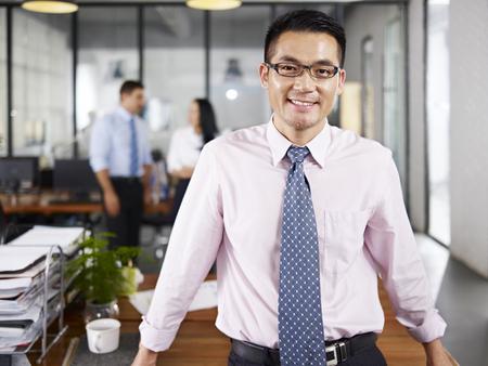 empresario: asi�tico de negocios de pie en la oficina feliz y sonriente con sus colegas multinacionales hablando en el fondo.
