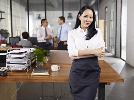 young asian businesswoman standing in office with multiethnic colleagues talking in background.