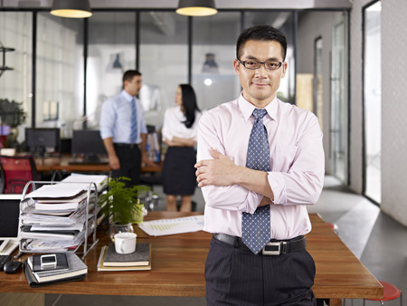 leader: asi�tico de negocios de pie en los brazos de la oficina cruzados con colegas multinacionales hablando en segundo plano. Foto de archivo