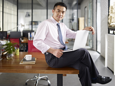 asian business person sitting on desk holding laptop computer in office. Stock Photo