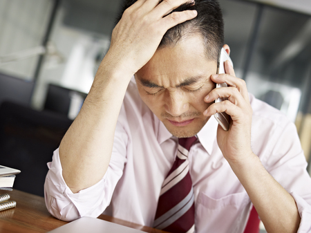 failing: asian businessman talking on cellphone looking sad and frustrated. Stock Photo