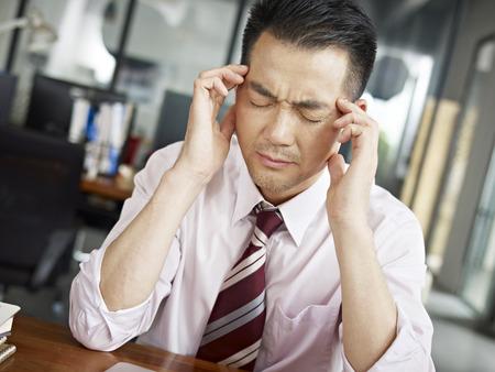 アジア系のビジネスマンがオフィスで頭痛を持ちます。