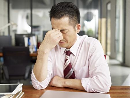 frustrace: Asijský podnikatel vypadal unaveně a frustrovaně v kanceláři. Reklamní fotografie