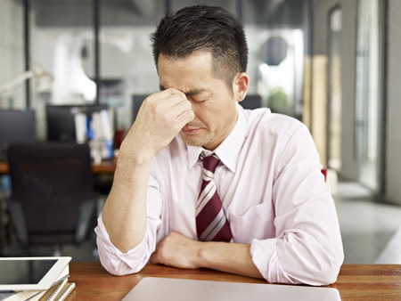 agotado: hombre de negocios asiático con aspecto cansado y frustrado en el cargo.