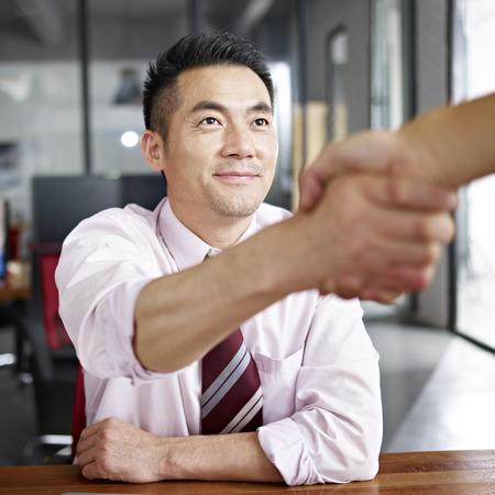 アジア系のビジネスマンがオフィスで来場者と握手します。