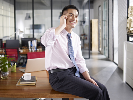asian business person sitting on desk talking on mobile phone in office.
