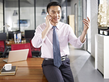 businesspeople: asian business person sitting on desk talking on mobile phone in office.