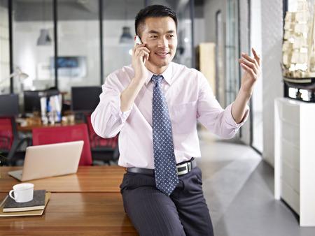person sitzend: asian Gesch�ftsmann sitzt auf Schreibtisch im Gespr�ch �ber Handy im B�ro.