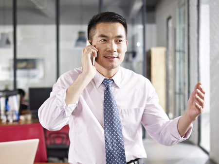 deal making: asian business person talking on cellphone in office.