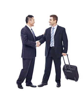 business traveler: caucasian businessman with suitcase greeted by asian partner, isolated on white background.