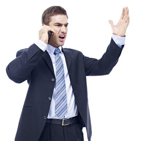 persona enojada: caucásico hombre de negocios hablando por teléfono celular, enojado, furioso, aislado sobre fondo blanco. Foto de archivo