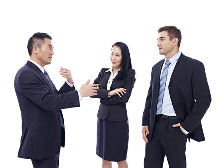 dialogo: la gente de negocios multinacionales que tienen una conversaci�n, aislado en fondo blanco. Foto de archivo