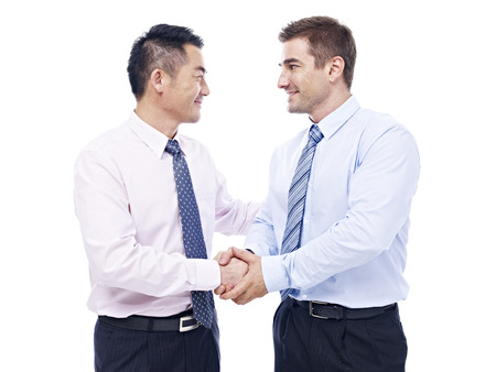 teaming up: asian and caucasian businessmen shaking hands looking at each other, isolated on white background.