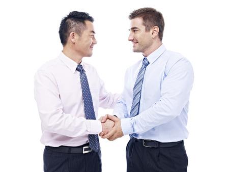 hommes d'affaires asiatiques et caucasien se serrant la main à se regarder, isolé sur fond blanc. Banque d'images