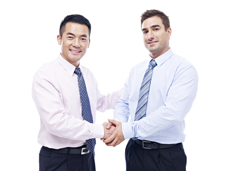 teaming up: asian and caucasian businessmen shaking hands looking at camera smiling, isolated on white background. Stock Photo