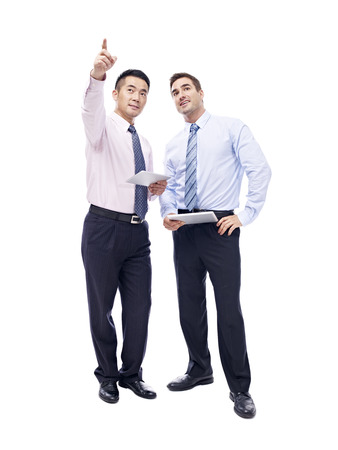 and white collar workers: asian and caucasian corporate executives standing and talking, isolated on white background. Stock Photo