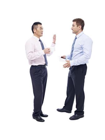 dos personas platicando: ejecutivos de empresas asi�ticas y cauc�sicas de pie y hablar, aislado en fondo blanco.