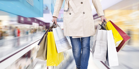plaza comercial: mujer caminando con bolsas de compras en un centro comercial.