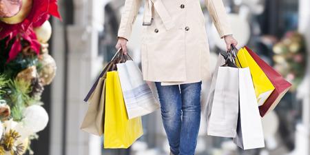 natale: donna che cammina con le borse della spesa con sfondo natalizio.