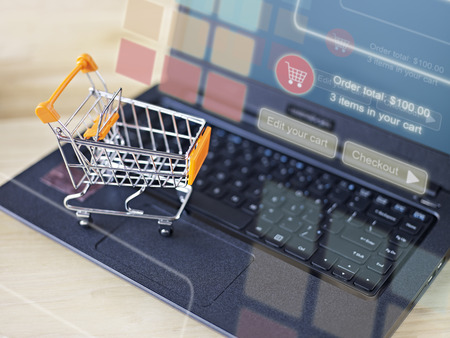 toy shopping cart on keyboard of laptop computer for online shopping and e-commerce concept.