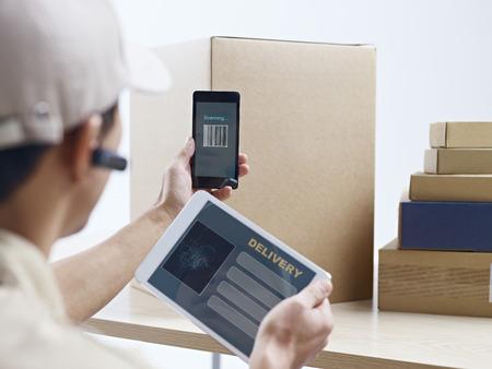 mâle travailleur de l'entreprise de messagerie asiatique en utilisant téléphone portable et ordinateur tablette à numériser des informations sur les paquets.