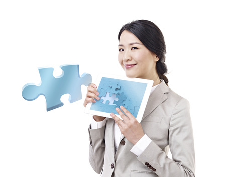 business puzzle: asian businesswoman showing tablet computer with one piece of jigsaw flying out of screen.