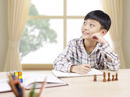 doing: 10 year-old asian elementary schoolboy looking away while studying at home. Stock Photo