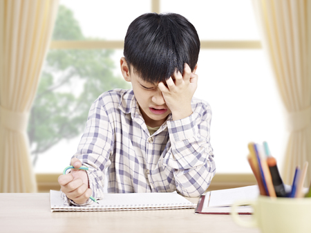 10 year-old asian elementary schoolboy appears to be frustrated while doing homework at home. Foto de archivo