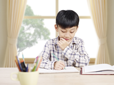 doing: 10 year-old asian elementary schoolboy studying andor doing homework at home. Stock Photo
