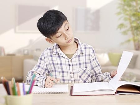 10 歳アジア小学生男子の勉強や宿題を家庭で。 写真素材