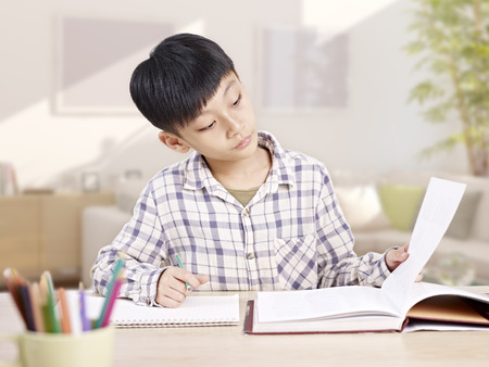 10 year-old asian elementary schoolboy studying andor doing homework at home. Stock Photo