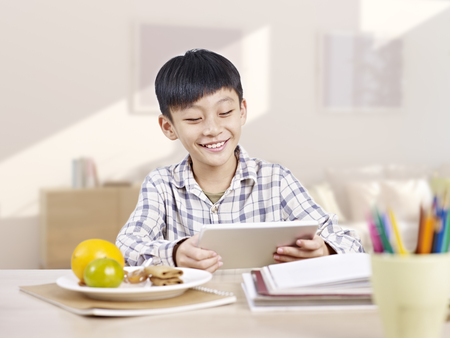 10 year-old asian elementary schoolboy looking at tablet computer and smiling. 免版税图像