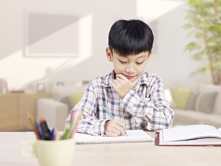 work at home: 10 year-old asian elementary schoolboy doing homework at home. Stock Photo