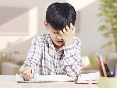 school work: 10 year-old asian elementary schoolboy appears to be frustrated while doing homework at home. Stock Photo