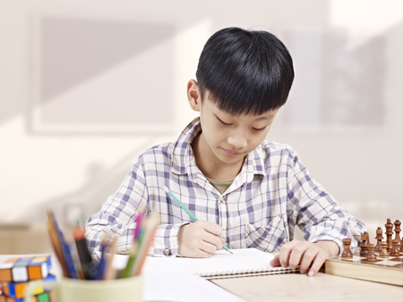 learning by doing: 10 year-old asian elementary schoolboy doing homework at home. Stock Photo