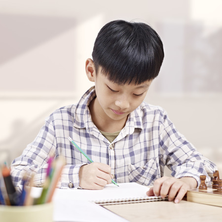 10 year-old asian elementary schoolboy doing homework at home. Stock Photo
