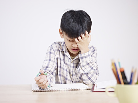 learning by doing: 10 year-old asian elementary schoolboy appears to be frustrated while doing homework. Stock Photo