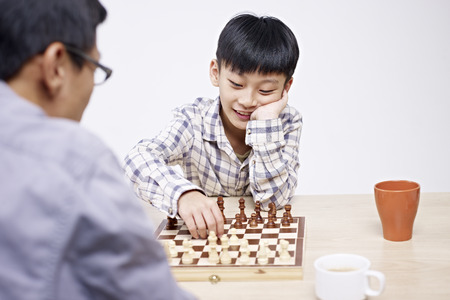 asian father playing chess with 10 year-old son.