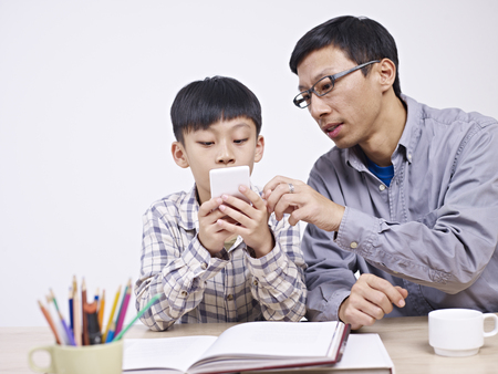 asian father and 10 year-old son playing with cellphone together. Stock Photo