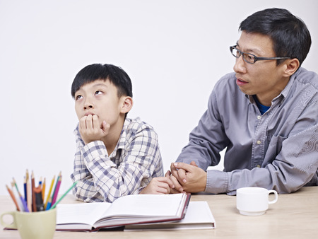asian father and 10 year-old son having a serious conversation. Stock Photo