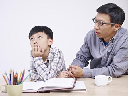 père asiatique et son fils de 10 ans ayant une conversation sérieuse.
