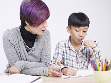 10 years old: asian mother helping 10 year-old son with homework. Stock Photo