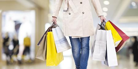 현대적인 쇼핑 센터에서 산책하는 다채로운 쇼핑 가방을 가진 여자.