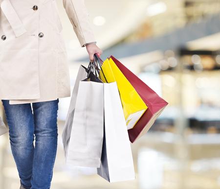 현대 쇼핑몰에서 산책하는 다채로운 쇼핑 가방을 가진 여자. 스톡 콘텐츠
