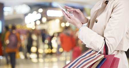 woman buying: hands of a young woman using mobile phone in modern shopping mall. Stock Photo