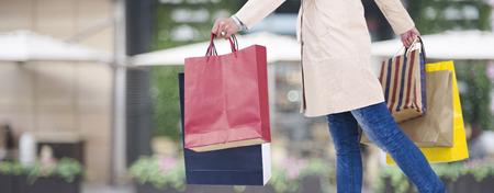 vrouw lopen op straat met kleurrijke boodschappentassen