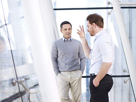 two caucasian business people having a casual conversation in modern office building.