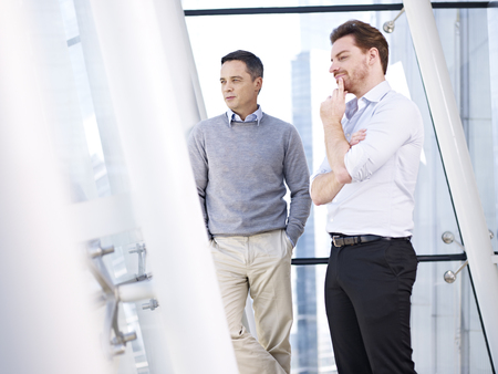 two hands: two caucasian business people looking out of window in modern office building.